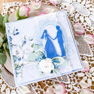 Ręcznie wykonana kartka ślubna w błękitnej kolorystyce. Kartka jest ozdobiona kompozycją kwiatową.